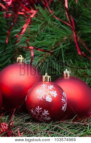 Three Red Christmas Balls And Xmas Tree Background