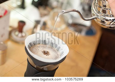 Professional male barista is brewing espresso in cafeteria