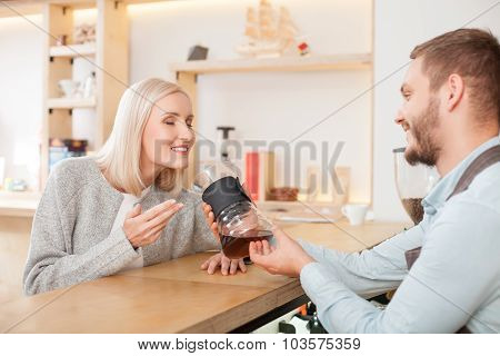 Cheerful young cafe owner in serving female customer