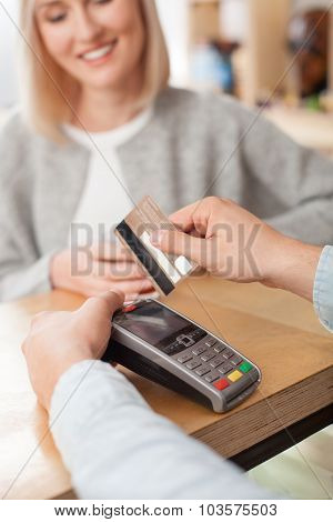 Cheerful male cafe worker is receiving payment