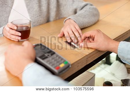 Cheerful lady is buying espresso in cafeteria