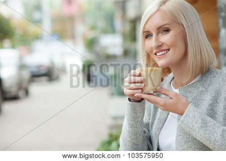 Attractive blond girl is relaxing with mug of latte