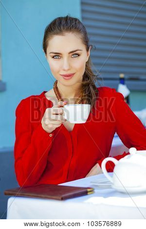 Young Brunette Woman Drinking Tea in a Cafe Outdoors. Summer City Background