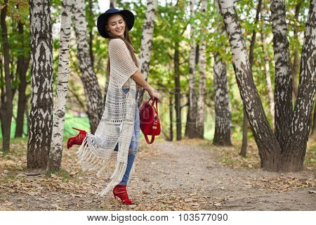 Young happy beautiful woman in blue jeans walking in autumn park