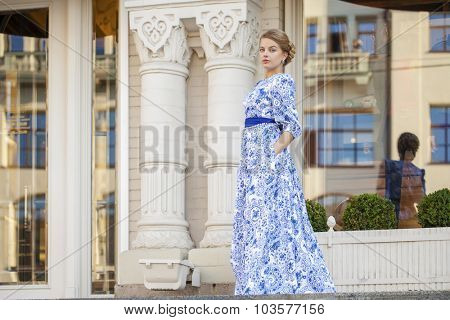 Young beautiful blonde girl in blue dress posing against a background of summer city