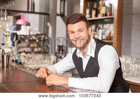 Handsome young barman is working in bar