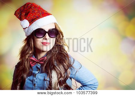 Confident girl in sunglasses wearing xmas santa hat