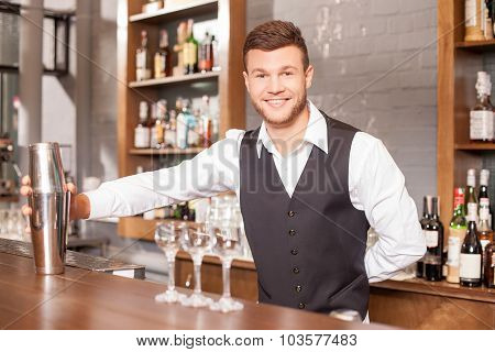 Cheerful young barman is making cocktails in bar