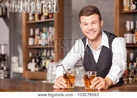 Handsome young bartender is serving his customer
