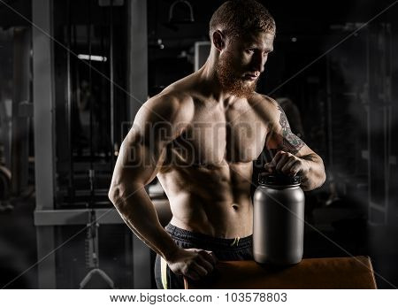 beautiful young athletic man holding a jar of sports nutrition