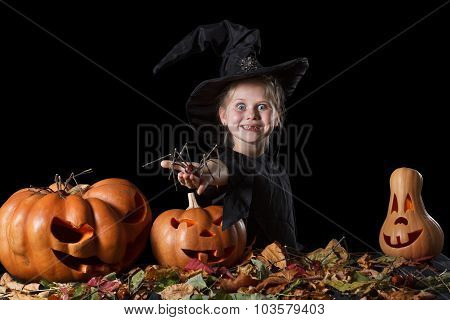Little witch enthusiastically holding a spider. Halloween.