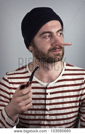 Lying bearded sailor grimacing while smoking a pipe