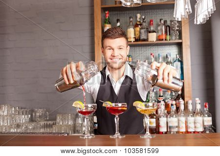Cheerful male barman is mixing beverage in bar