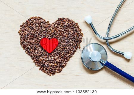 Buckwheat Groats Heart Shaped On Wooden Surface.