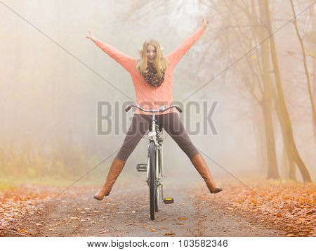 Active Woman Having Fun Riding Bike In Autumn Park