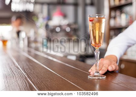 Professional male bartender is serving drink in pub