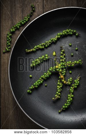 Green Peppercorns In Old Pan On Rustic Wood Background