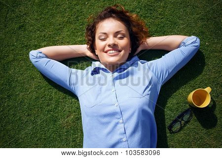 Positive girl lying on the grass