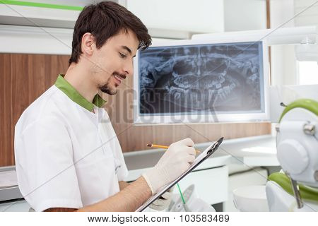 Attractive male dentist is analyzing teeth in office