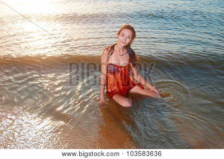 Young beautiful redhair girl in azure bikini and orange tunic posing on the beach