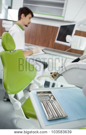 Dental office with attractive young male dentist in background