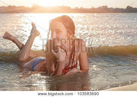Smiling beautiful woman in bikini lying on a beach and smiling