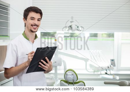 Attractive male dental doctor is working in his office