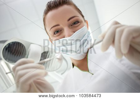 Cheerful female dental doctor is working in her office
