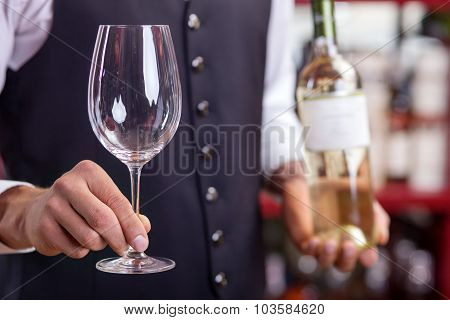 Skilled young male sommelier is working in bar