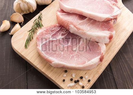 Raw Pork Chop Steak And Garlic, Pepper On Wooden Background