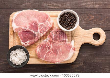 Top View Raw Pork Chop Steak On Wooden Background