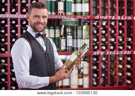Cheerful male waiter is working in wine-cellar
