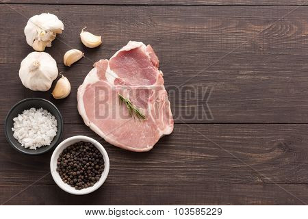Top View Raw Pork Chop Steak And Garlic, Pepper, Salt On Wooden Background
