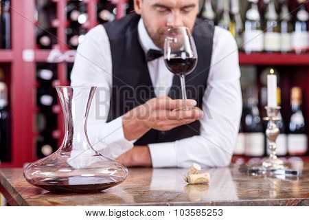 Handsome young male waiter is tasting red drink