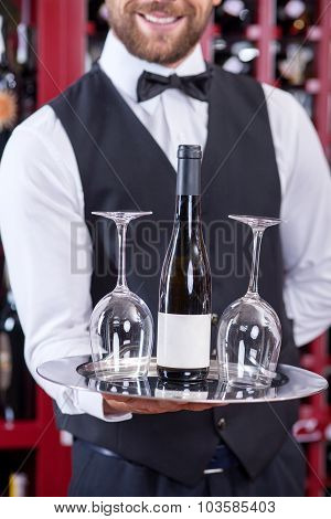 Cheerful young waiter is serving wineglasses for drinking