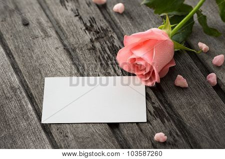Single Pink Rose With Drops Of Water And White Blank Note On Wooden Old Background, Horizontal Compo