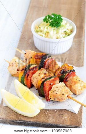 Light summer lunch grilled chicken and vegetable skewers served with coleslaw side salad