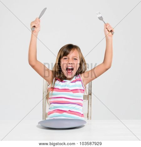 Hungry angry young girl screaming, shouting, throws a tantrum, raises arms holding cutlery at a table with empty plate