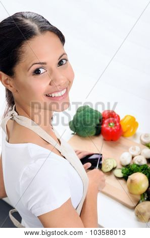 Happy asian woman looks over her shoulder while slicing and preparing food in the kitchen