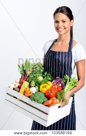Portrait of smiling mixed race woman chef holding a crate full of fresh organic vegetables on grey background, promoting eating seasonally and sourcing from local producers