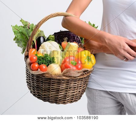 Woman holding basket of raw organic vegetables part of her household purchase, healthy living concept
