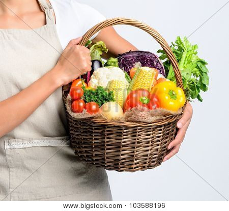 Anonymous young woman holding a basket full of fresh organic vegetable produce on grey background, promoting healthy diet and lifestyle