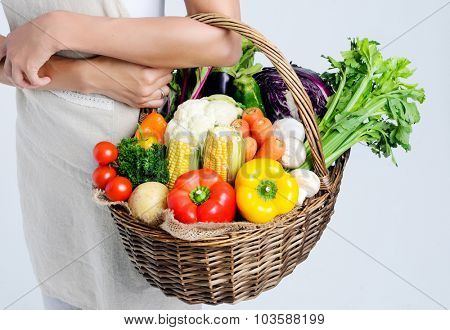Woman holding basket of fresh organic vegetables from the farmers market
