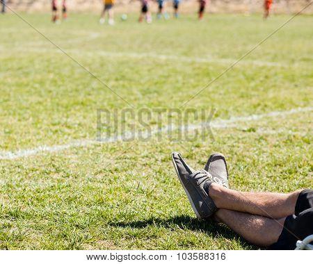 mans legs relaxing on a soccer grass field