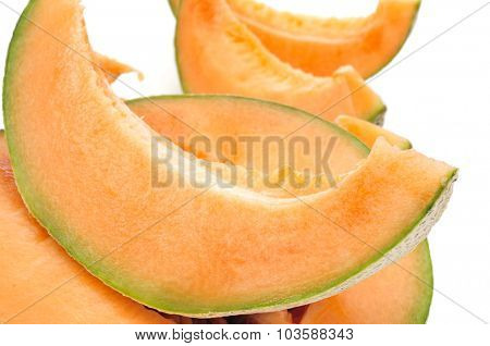 closeup of some slices of Persian melon on a white background