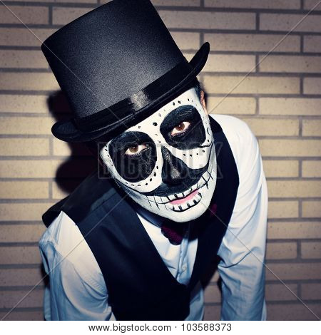 a man with calaveras makeup, wearing bow tie and top hat, against a brick wall