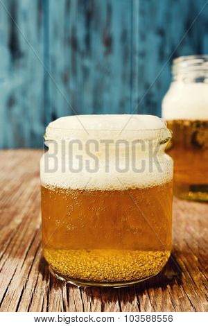 refreshing beer served in glass jars on a rustic wooden surface