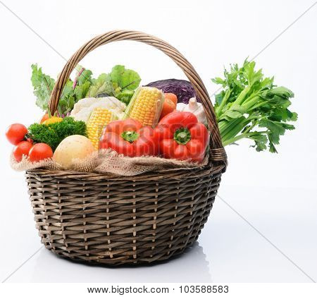 Basket of fresh raw organic vegetable produce, assortment of corn, peppers, broccoli, mushrooms, beets, cabbage, parsley, tomatoes, isolated on light background