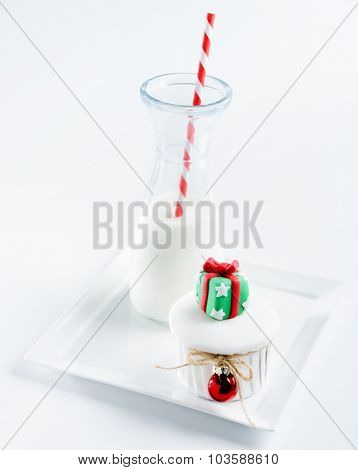 Seasonal holiday christmas theme mini cake cupcake with decoration bauble and ribbons served with milk