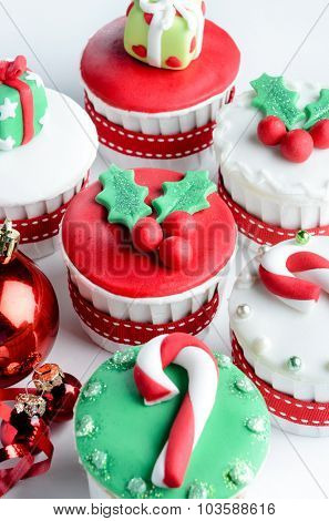 Seasonal festive christmas mini dessert cupcakes in traditional red green decorative symbols elements